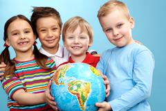 group of adorable boys and girl with globe - stock photo