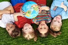 Group of happy children lying on a green grass with globe Stock Photos