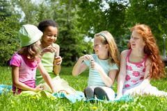 portrait of cute girls having fun on green lawn in park - stock photo