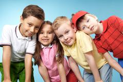 Stock Photo of group of adorable kids looking at camera on blue background