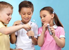 Group of adorable kids with soap bubbles on blue background Stock Photos