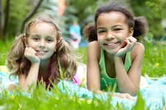 Portrait of two cute girls having rest in park on summer day Stock Photos