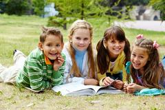 Portrait of cute kids lying on lawn and looking at camera with open book near by Stock Photos