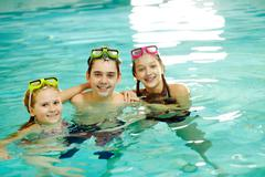photo of happy friends looking at camera in pool - stock photo