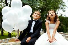 Portrait of children bride and groom with balloons sitting in park Stock Photos