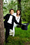 portrait of cute boy groom and girl bride in the park - stock photo