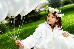 portrait of girl bride with balloons sitting in park - stock photo
