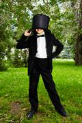 portrait of boy groom in tuxedo posing in the park - stock photo