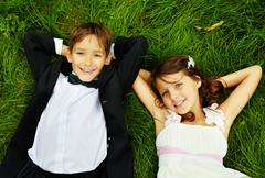 Portrait of smiling children bride and groom lying on green grass and looking at Stock Photos