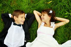 Stock Photo of portrait of smiling children bride and groom lying on green grass and looking at