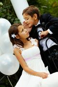Portrait of boy groom whispering secret to his bride Stock Photos