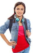 Stock Photo of cute girl with backpack and headphones smiling at camera in isolation