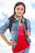 cute girl with backpack and headphones smiling at camera in isolation - stock photo
