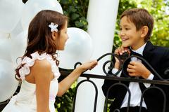 Portrait of boy groom and his cute bride chatting in park Stock Photos