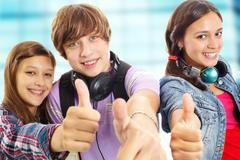 cute teens with headphones showing thumbs up and smiling at camera - stock photo
