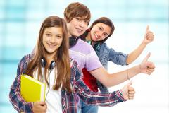 row of teens with headphones showing thumbs up and smiling at camera - stock photo