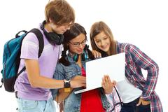 Three teenagers studying with laptop Stock Photos