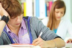 Portrait of smart guy making notes in copybook with his classmate behind Stock Photos