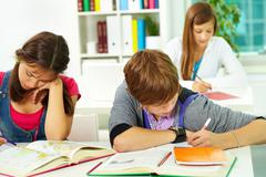 portrait of smart guy making notes in copybook with his classmates near by - stock photo