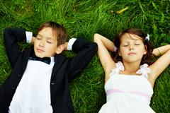 Portrait of calm children bride and groom lying on green grass Stock Photos