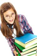 Stock Photo of cute girl with big stack of books smiling at camera in isolation