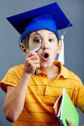 portrait of curious boy in graduation hat looking through magnifying glass - stock photo