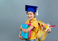 portrait of happy schoolkid with backpack and books - stock photo