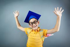 portrait of happy schoolkid with backpack raising arms - stock photo