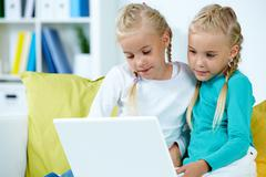 Stock Photo of portrait of twin girls studying in front of laptop