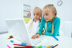 Portrait of twin girls studying in front of laptop Stock Photos