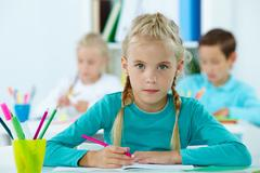 portrait of lovely girl drawing with classmates on background - stock photo