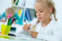 Stock Photo of portrait of lovely girl drawing with highlighters