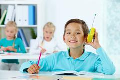 portrait of cute lad listening to radio while drawing with classmates at lesson - stock photo