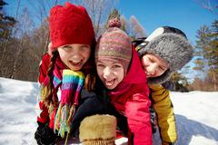 happy friends in winterwear looking at camera while having fun outside - stock photo