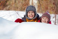 happy friends in winterwear peeking out of snowdrift outside - stock photo