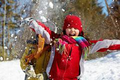 happy friends in winterwear playing with snow in park - stock photo