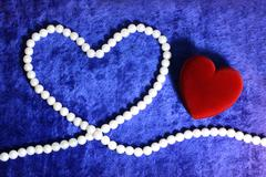 Red heart and pearly neacklace on blue velvet Stock Photos