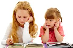 portrait of cute girls reading interesting books - stock photo