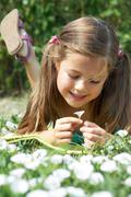 close-up of girl lying on green grass and enjoying nice smell of tiny flower - stock photo