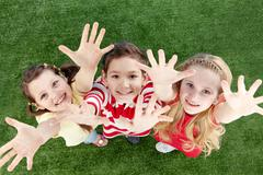 Image of happy friends on the grass raising arms Stock Photos