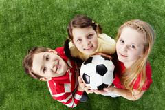 Image of happy friends on the grass with ball looking at camera Stock Photos
