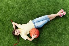 image of happy girl lying on the grass with ball and looking at camera - stock photo