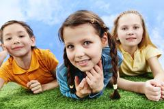 image of happy girl lying on the grass and looking at camera with friends at bac - stock photo