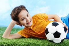image of happy boy lying on the grass with ball and looking at camera - stock photo