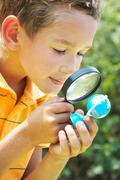 Portrait of cute schoolboy looking at small globe model through spy glass in nat Stock Photos