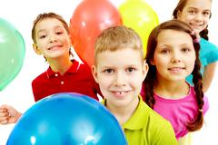 Portrait of children with balloons looking at camera Stock Photos