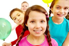 portrait of smiling kids holding colorful balloons with girl in front - stock photo