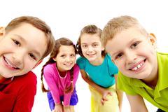 group of joyful children peeping into camera - stock photo