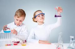 A little boy pouring liquid into a tube and his assistant shaking a flask Stock Photos