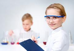 a little girl in protective glasses making notes and looking at camera - stock photo